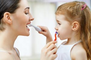 A woman and child brushing each other's teeth.