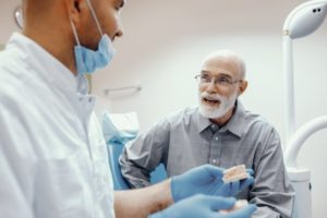an older man talking to his dentist about dentures