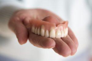 Someone holding a full upper denture