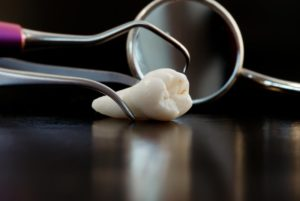 An extracted tooth lying on a table with dental instruments surrounding it