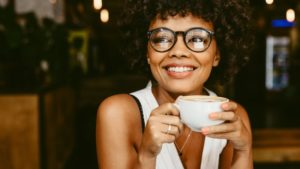 Woman drinking a cup of coffee safely after tooth extraction in Orlando