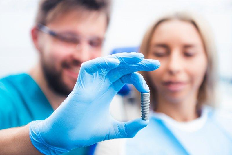 Dentist's gloved hand holding a single dental implant
